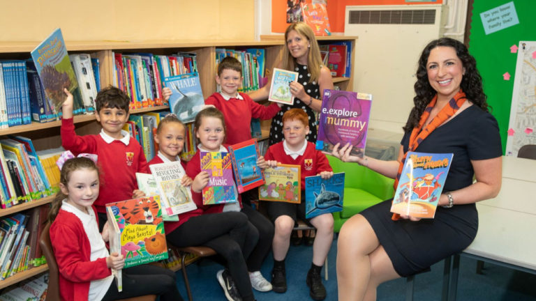 Manchester house builder boosts school library with book donation